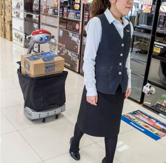 ショッピング中の利用客の後ろをBudgeeが荷物を運ぶ