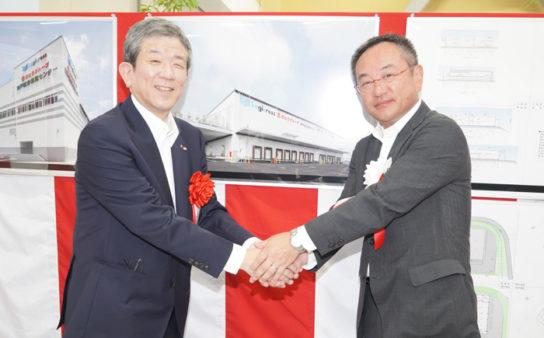 竣工式で握手するさとうの佐藤社長(左)と三菱地所の細包執行役常務(右)