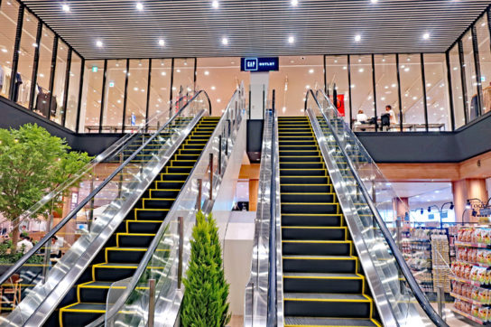 店舗中央に2階アウトレットへのエスカレーターを配置