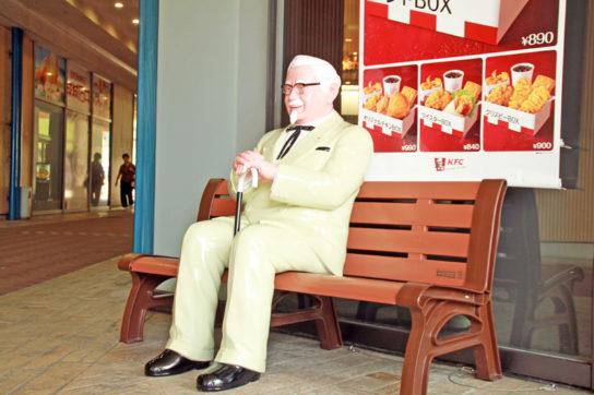 ベンチに座った新カーネル・サンダース像